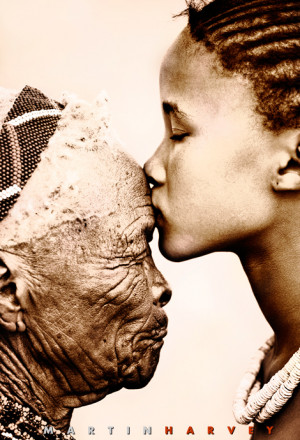 Young San girl kissing old woman on forehead.