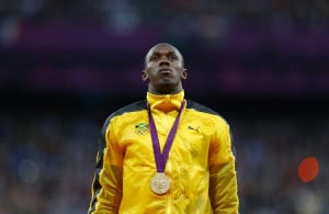 Usain Bolt stands on the podium during the medal ceremony for the 100m ...