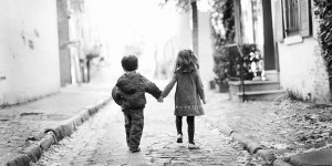 Captured moment of two child friends holding hands.