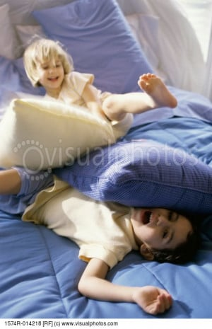 brother_and_sister_having_a_pillow_fight_on_the_1574r-014218.jpg