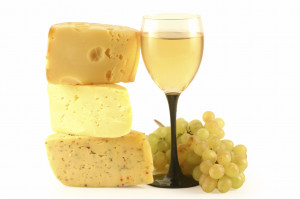 Grapes, cheese and a glass with wine isolated on white.