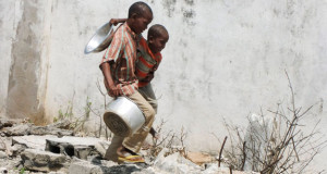 Two Somali children walk to a food distribution center