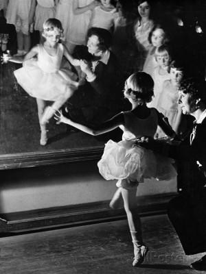 Ballet Teacher Advising Little Girl and Group of Dancers at Ballet