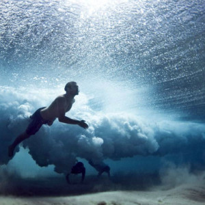 underwater_photo_of_swimmers_under_a_wave
