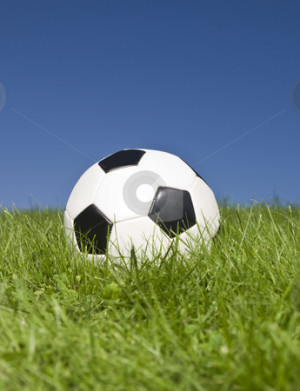 Black and white football in green grass. stock photo, Black and white