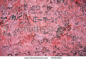 Grunge background of graffiti and sayings carved on a red wall