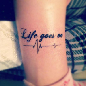 17. Life quote tattoo on legs