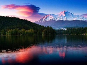 Nature scene of trees and mountains reflection in lake at sunset