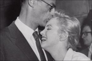 Marilyn Monroe leans against her fiance, playwright Arthur Miller, as ...