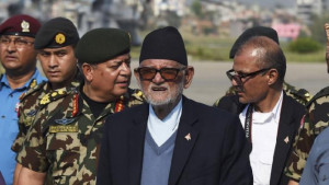 Nepalese Prime Minister Sushil Koirala (C) walks on the tarmac at the ...