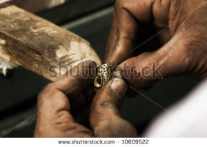 holding an unfinished 22 carat gold earring in his hard working hands ...