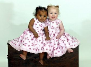 ... : Photographs show a pair of black and white fraternal twin girls