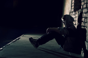 lonely_boy_sitting_on_street