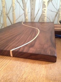 Walnut bread board with curved maple strip. By Jody More