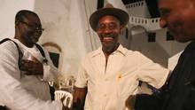 Poet Linton Kwesi Johnson (C) talks with friends at Elmina castle in ...