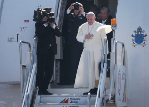 Pope Francis waves from the steps of his aircraft as he leaves ...