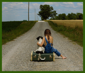 girl sitting with a dog on a suitcase