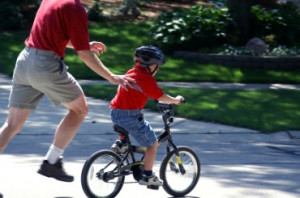 He is teaching his son how to ride a bicycle.