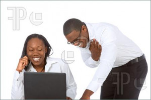 African-American young Couple by laptop laughing