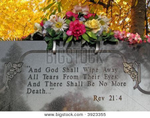 silk flowers on a cemetery grave tombstone revelations bible verse
