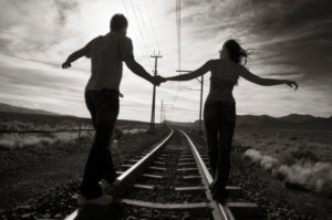 Young couple walking hand in hand on train track, rear view (B&W)