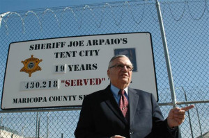 Maricopa County Sheriff Joe Arpaio stands in front of a sign touting ...