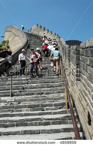 Tourists climbing stairs on the Great Wall of China - stock photo