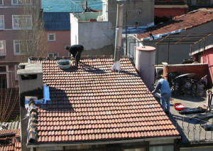 Watching cement liberally applied on top of roof tiles...]