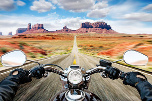Man riding motorcycle on dirt track, Monument valley in background