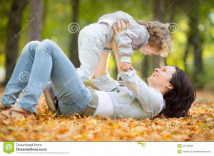 Happy family having fun outdoors in autumn park against blurred leaves ...