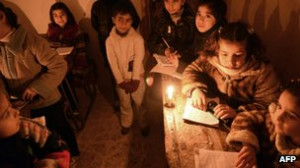children attend an early morning class by candle light due to the lack ...