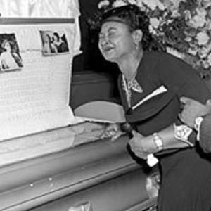 Emmett Till's mother at his open coffin.