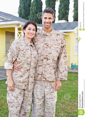 Military Couple In Uniform Standing Outside House Smiling.