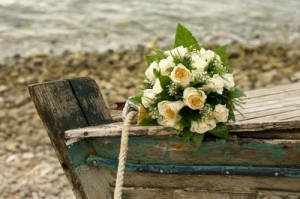 ... of ivory-colored roses set on a boat hull after a beach wedding