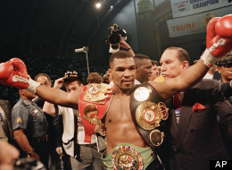 Mike Tyson shows off his three heavyweight title belts following his ...