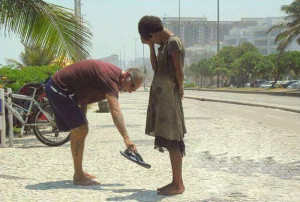 man giving his shoes to a homeless girl in Rio de Janeiro.