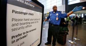 TSA officer waves passengers toward a security checkpoint in Seattle ...