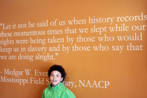 ... (7th grade) standing in front of a powerful Medgar Evers quote