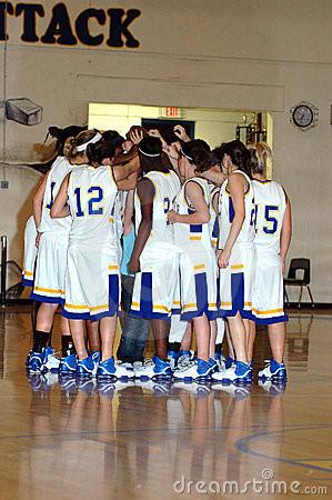 Huddle of high school girls basketball team.