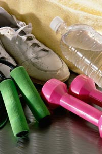 close-up on an athletic shoe, water bottle, free weights, and a towel