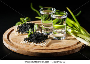 Vodka and black caviar on black background - stock photo