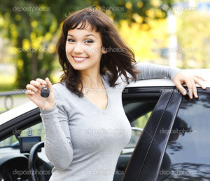 Pretty girl showing the car key - Stock Image