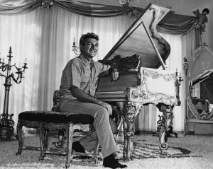 Liberace sitting at a lavishly-decorated gold-leaf piano in the living ...