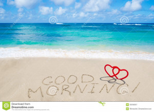 Sign Good morning with two hearts on the sandy beach by the ocean.