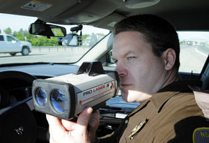 North Dakota State Trooper Jamey Jahner uses a laser speed gun along ...