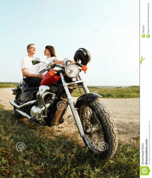 Young biker couple on the country road against the sky.