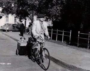 Edgar Bergen and Charlie McCarthy ride a bike. Mortimer Snerd, in the ...