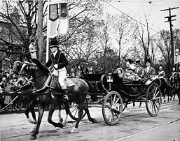 George VI and Queen Elizabeth in a landau with footmen and an outrider ...
