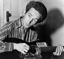 Woody Guthrie with guitar labeled