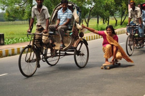 Girl Skateboarding By Rickshaw